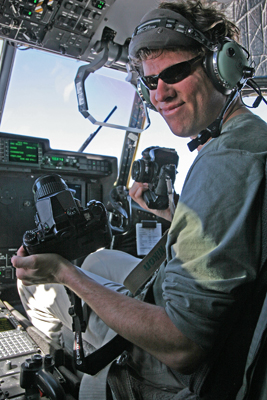 Author / Photographer Ed Darack holding two of his cameras in the right seat of a Marine Corps KC-130J flying thousands of feet above the Al Anbar Province of Iraq. Copyright Ed Darack; Permission granted for use in media products about / related to Ed Darack's creative work. width=